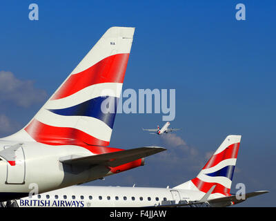 British Airways plane taking off and two BA tail fins, London City Airport, London, Britain, UK - Stock Image