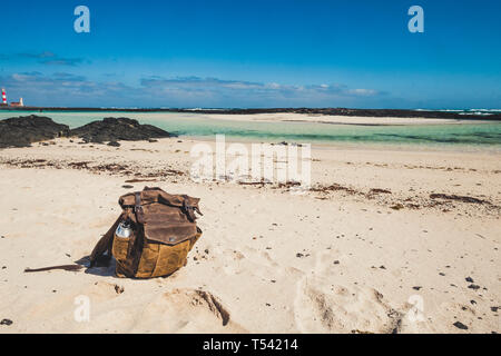 Vintage beautiful leather backpack at the beach for travel summer holiday vacation concept - tropical sand and blue background - Stock Image
