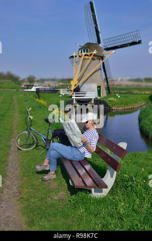 Woman cyclist studying map with the Hoop Doet Leven Windmill in the background.  Voorhout, Holland, the Netherlands - Stock Image