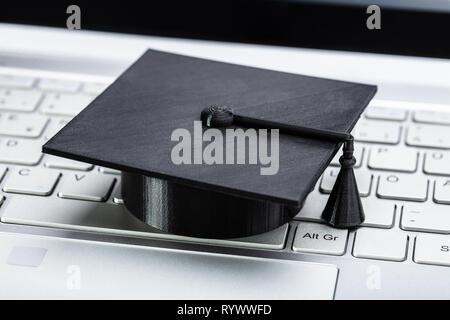 Close-up Of Black Graduation Hat On Laptop Keypad - Stock Image