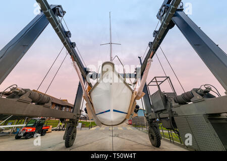 sailing yacht in a hoist at a boatyard waiting to be launched - Stock Image
