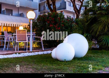 Big white decorative balls on the grass near a restaurant. - Stock Image