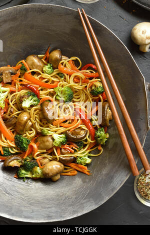Close up of stir-fry noodles with vegetables in wok pan on black stone background. Top view - Stock Image