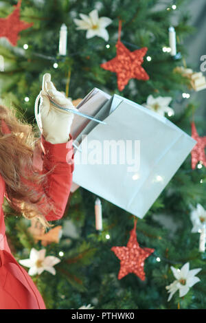 cheerful modern woman in red trench coat with shopping bags and Christmas present box near Christmas tree - Stock Image