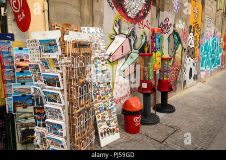 Portugal, Porto, Avenida Dom Afonso Henriques, souvenirs on display by graffiti covered wall - Stock Image