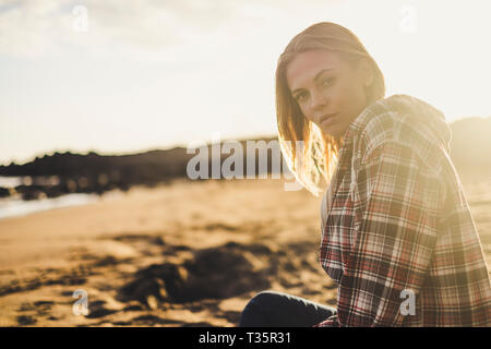 Golden colours sunset and beautiful hipster blonde woman sit down on the sand at the beach enjoying the outdoor nature and the magic moment of vacatio - Stock Image