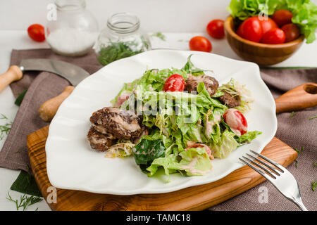 Salad with beef, lettuce, cherry tomatoes, and mayonnaise dressing. Cafe menu on a wooden background in warm colors with copy space. - Stock Image