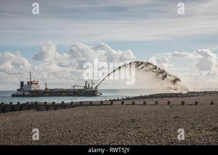 Suction hopper dredger performing beach restoration on Eastbourne beach England UK. - Stock Image