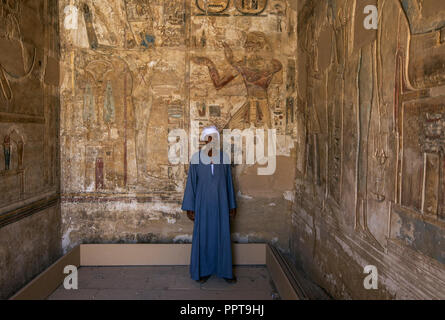 Egyptian man standing inside the tomb in Temple of Ramses III at Medinet Habu in Luxor, Egypt - Stock Image
