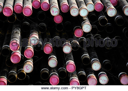 Stack of pipes with pink lids - Stock Image