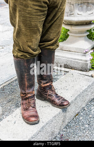 Well worn leather gaiters and boots and corduroy trousers worn by a farm worker. - Stock Image