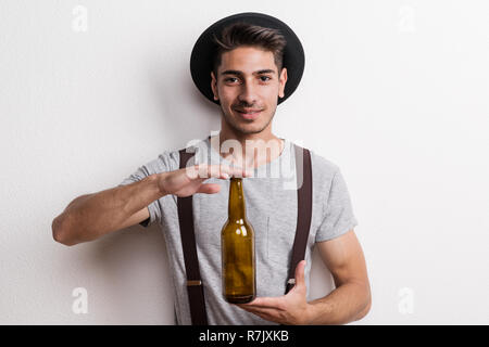 A portrait of confident young man with suspenders and black hat in a studio, holding empty beer bottle. - Stock Image