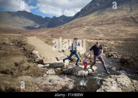 Family crossing stream, Fairy Pools, Isle of Skye, Hebrides, Scotland - Stock Image