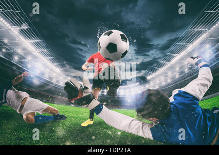 Close up of a football action scene with competing soccer players at the stadium during a night match - Stock Image