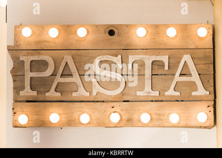 Pasta sign made of wooden planks and light bulbs on top and bottom - Stock Image
