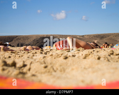 People lying in the sun on a naturist beach Lanzarote.No-one is recognisable and no private body parts are visible.Red - Stock Image