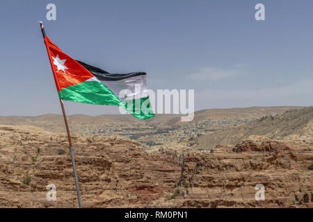 The Jordanian flag ripples in the wind over Petra in Jordan. - Stock Image