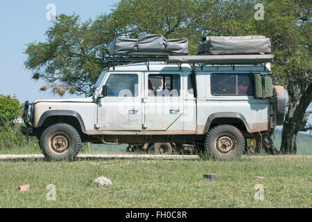 Old Land Rover Defender 110  with two roof tents Parked at roadside refreshment van Tanzania - Stock Image