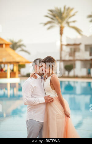 Happy newlyweds hug and smile next to the swimmimg pool on background of palms during the honeymoon in Egypt. - Stock Image