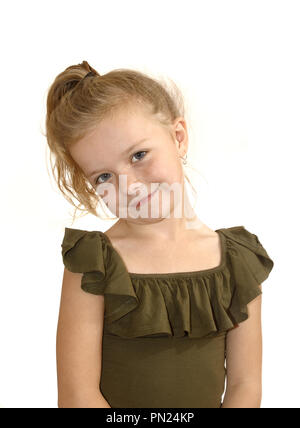 Six year old girl, with head tilted, smiling at camera - Stock Image
