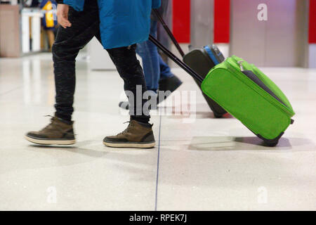 People walking with hand luggage through airport terminal in Dublin, Ireland - Stock Image
