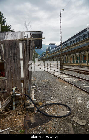 Neglected water pumping facility next to the railways at Canfranc International railway station front (Canfranc, Pyrenees, Huesca, Aragon, Spain) - Stock Image