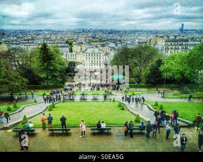 City day views of Paris in Spring as seen from Montmarte hill in France. Tourists in foreground, Montparnasse Tower - Stock Image