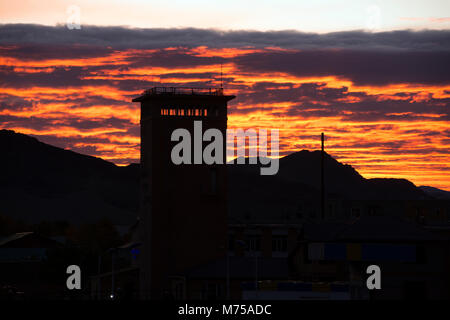 One of the tallest buildings in the western Mongolian city of Ölgii is silhouetted against the rising sun. - Stock Image