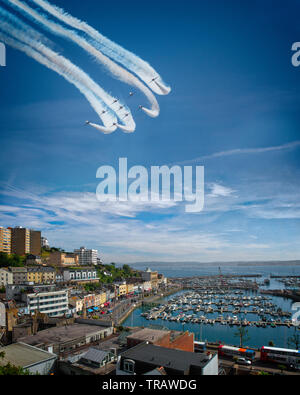 GB - DEVON: RAF Red Arrows Display Team over Torbay with Torquay harbour and town in the foreground. (Torbay Airshow, a two-day event 1st June and 2nd - Stock Image