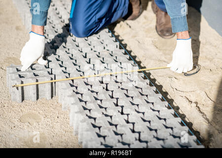 Builder measuring paving tiles with holes for grass on the construction site, close-up view from above - Stock Image