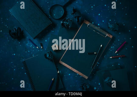 Clipboard, notes and a magnifying glass black on black flat lay. Starry sky background. Science and research concept. - Stock Image