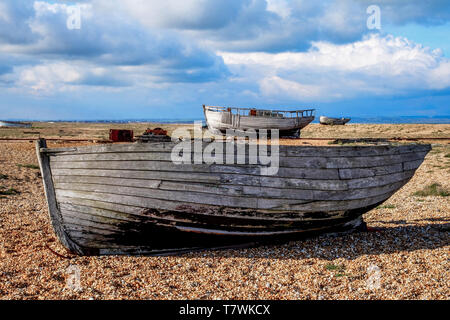 an old wooden fishing boat sitting on a pebble beach, in the back ground on the beach are two more old wooden fishing boats, the pebbel beach is flat  - Stock Image