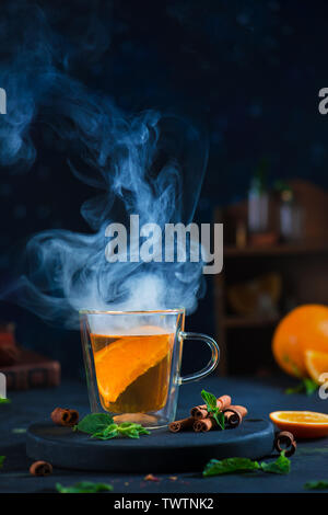 Double wall glass cup with citrus tea, cinnamon, and mint leaves. Steam in dark food photography with copy space. - Stock Image
