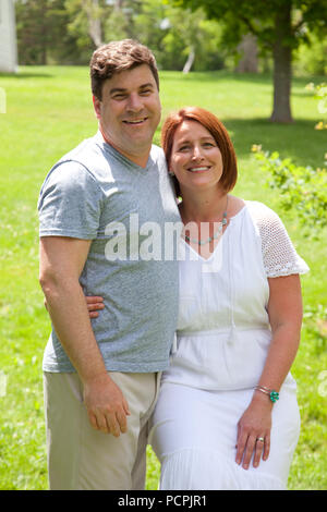 A happily married man and woman pose for a photo on a sunny day outside - Stock Image