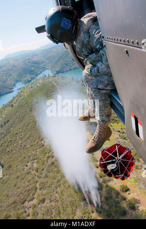 Sgt. Julian Ross of the 2-135th Aviation Regiment, based out of Mather, hit the buttom releasing water on target - Stock Image