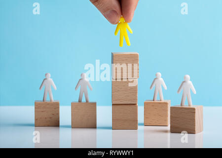 Hand Placing Human Figure Over Stacked Wooden Block On White Desk - Stock Image