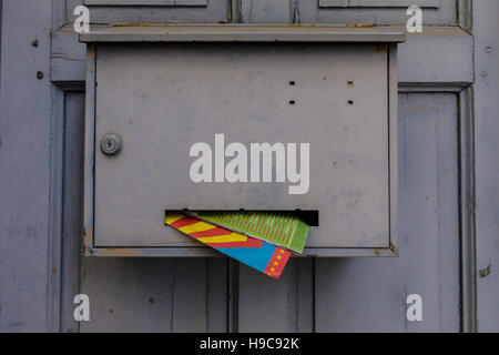 A mailbox in France with colourful mail sticking out. Seen in the village of Ramatuelle, South of France. - Stock Image