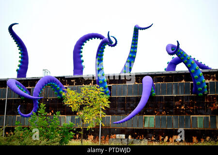 Philadelphia, USA. 8th Oct 2018. Inflatable tentacles of a temporary art installation, titled Navy Yard Sea Monster, by British artist Pedro Estrellas and Filthy Luker appear to emerge from an old warehouse in Philadelphia, Pennsylvania, on October 8, 2018. The art work is commissioned by Philadelphia Industrial Development Corporation to promote the redevelopment of Philadelphia Navy Yard. Credit: PhotograPHL/Alamy Live News - Stock Image