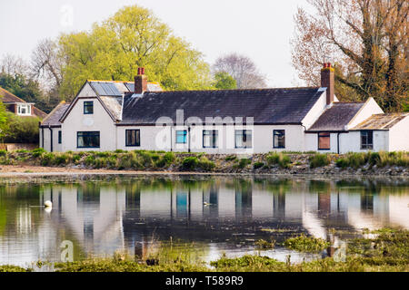 The National School 1834 converted into a house reflected in the creek at high tide. Bosham, Chichester, West Sussex, England, UK, Britain - Stock Image