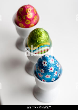 Chocolate Easter Eggs in egg cups: A row of three eggs in three white porcelain egg cups on a white background. - Stock Image