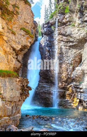 Upper Falls at Johnston Canyon in Banff National Park flowing into the turquoise colored creek. Johnston Canyon is a popular hiking spot in the Canadi - Stock Image