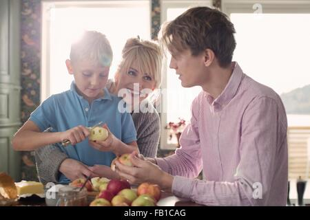 Parents and son peeling organic apples in kitchen - Stock Image