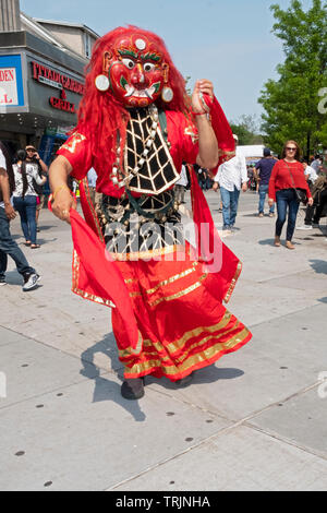 A Nepalese man in a traditional Himalayan Lakhey mask dances in Diversity Plaza in Jackson Heights, Queens, New York. - Stock Image