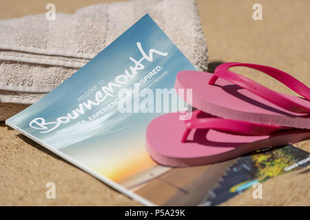 Bournemouth, UK. 26th June 2018. UK Weather, a heatwave in June. Sandy beach in Bournemouth with towels and flip flops with the tourist information guide book. Credit: Thomas Faull / Alamy Live News - Stock Image