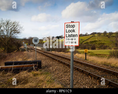 Un-gated level crossing sign Stop Look Listen Beware of trains, a compulsory whistle sign for the train and a 20 mph speed limit on the bridge ahead - Stock Image