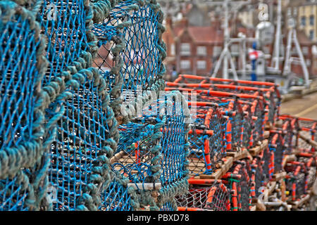 Lobster and crab pots piled high along the dock side of Scarborough's harbour. - Stock Image