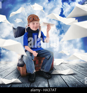 A little child is holding a paper airplane in the sky dreaming about being a pilot flying. The boy is happy for - Stock Image