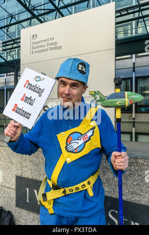 London, UK. October 19th, 2018. 'Commander Neil Godwin Tracy' of International Rescue poses with his ship Thunderbird 2 outside the Dept for Business, Energy and Industrial Strategy (BEIS).  He had come to offer his organisation's assistance, to produce policies which which recognise the desperate need to cut carbon emissions to avoid disastrous global warming and climate change by banning all fracking. Credit: Peter Marshall/Alamy Live News - Stock Image