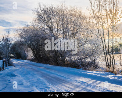 A narrow country lane in the snow. - Stock Image