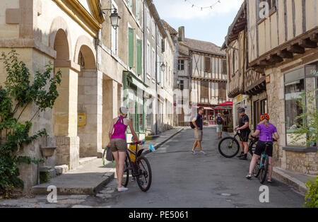 People cycling in the bastide town of Issigeac in the Dordogne, France Europe - Stock Image
